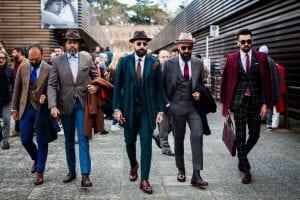 Cinque uomini che cammina con giacca e cappello.
