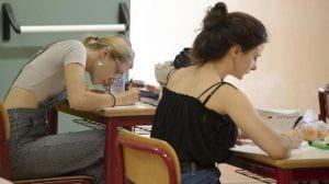 Ragazze sedute a un banco scrivono.