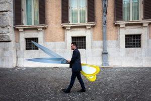 Uomo cammina con delle forbici enormi davanti all'edificio del Parlamento.