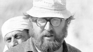 volto d'uomo con occhiali e cappello e dietro donna velata