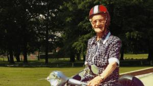 Vecchia signora con casco in moto
