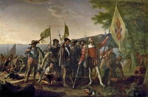 Painting of Christopher Columbus landing in the New World. He and his soldiers raise Spanish flags, while Native Americans bow in fear.
