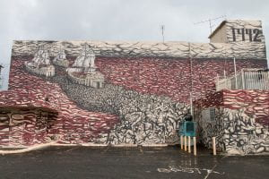 Mural on outside of building in San Juan showing Columbus' three ships sailing away from the New World through a red sea of blood, leaving bodies in their wake