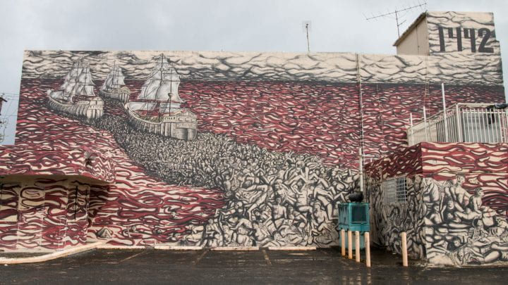 Mural in San Juan showing Columbus' three ships sailing away from the New World through a sea of blood, bodies in their wake