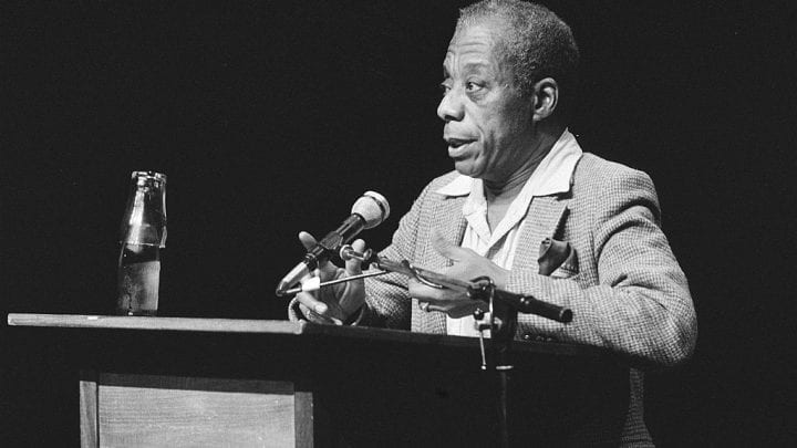 James Baldwin speaking from a lectern with microphone, black and white