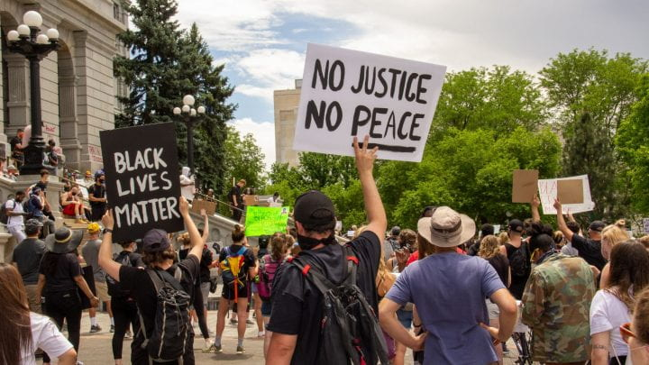 Protesters holding signs saying No Justice, No Peace, and Black Lives Matter