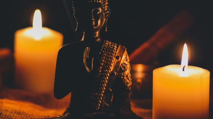 Seated Buddha statue surrounded by candles