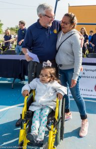 Morris and a mom hug after her daughter receives a new wheelchair. [photo credit: American Wheelchair Mission]