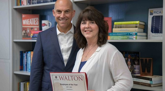 Dean Matt Waller recognizes Kim Miller as the 2018 Employee of the Year for Walton College.