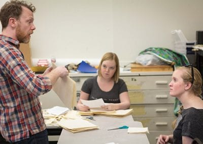 Smith instructs students Nina Andersen (left) and Kendra Grant in the art of folding their cut manuscript pages. (Yes, they had scissors in medieval times!)