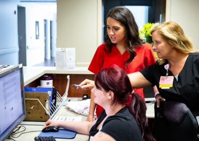 Childers explains the survey to Willow Creek staffers Debbi Neece (right) and Lidia Price;