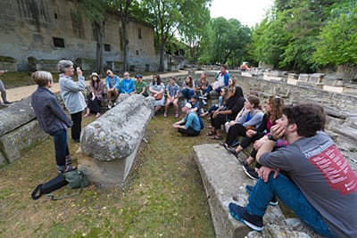 Students perch on tombs while Dean Lynda Coon discusses martyrs at Alyscamps, a Roman necropolis in Arles