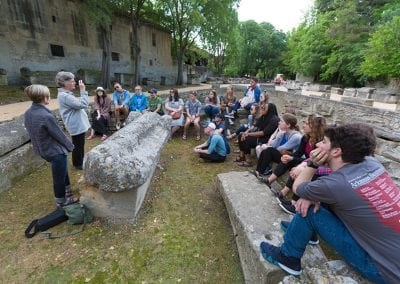 Students perch on tombs while Dean Lynda Coon discusses