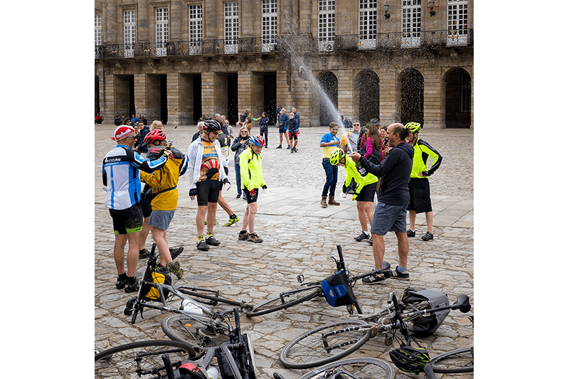 A group of cyclist pilgrims celebrate in front of the Cathedral of Santiago de Compostela