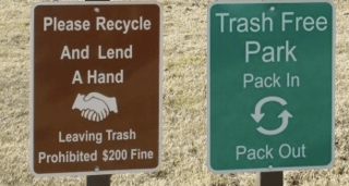 "A brown sign (left) reads: ""Please Recycle and Lend a Hand; Leaving Trash Prohibited $200 Fine."" A green sign (right) reads: ""Trash Free Park; Pack In, Pack Out."""