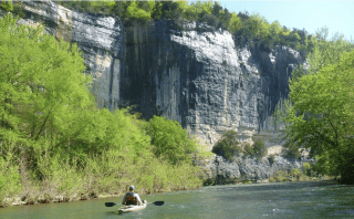 A man kayaking under large bluffs on the Upper Buffalo River.