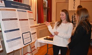 Paige Sellen, left, talks with Caroline Fortson, both U of A nursing students, about her research on yoga's influence on children's behavior. Fortson's research was about improving physical fitness in elementary-age children.