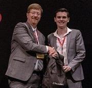 Johnny Key, Arkansas commissioner of education, presents an award to Nate Vogel.