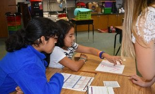Students use plastic pieces for a math lesson.