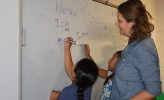 Students practice writing – and revising – on a white board.