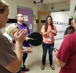 A participant plays a drum during a workshop for teachers to learn how to integrate music into math, literacy, social studies, and science.