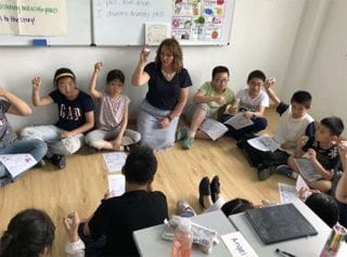 Jennifer Wiggins, a fifth-grade teacher in Springdale, works with children during a recent trip to China.