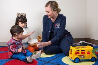 A graduate student works with children with hearing loss at the U of A Speech and Hearing Clinic.