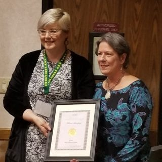 Melanie Landrum, right, receives honor from LaDawna Dillman of Arkansas Arts Educators