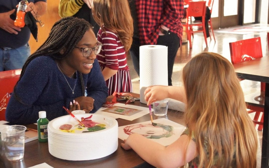Jada Miller, Dean's Spotlight, helps a child with crafts during Arkansas Hands and Voices event