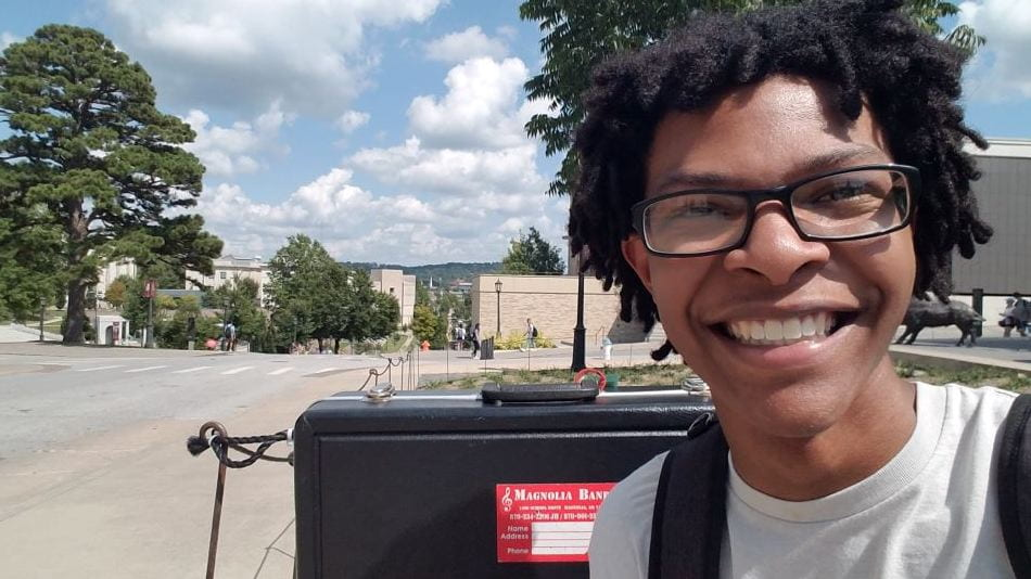 U of A student Terrell Page smiles at the camera with the U of A campus in the background
