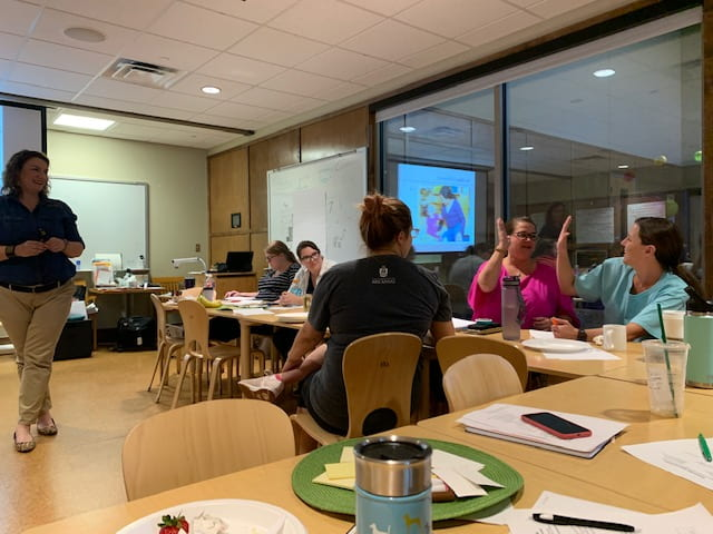 Two women high-five in the background while sitting at a table with instructors during a workshop at the September Professional Educator Development Day at the Jean Tyson Child Development Study Center at the University of Arkansas.