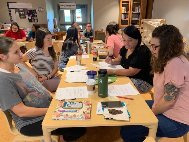 Four women sit at a table in the foreground, reading their papers, while other women sit at tables in the background during a workshop at the September Professional Educator Development Day at the Jean Tyson Child Development Study Center at the University of Arkansas.