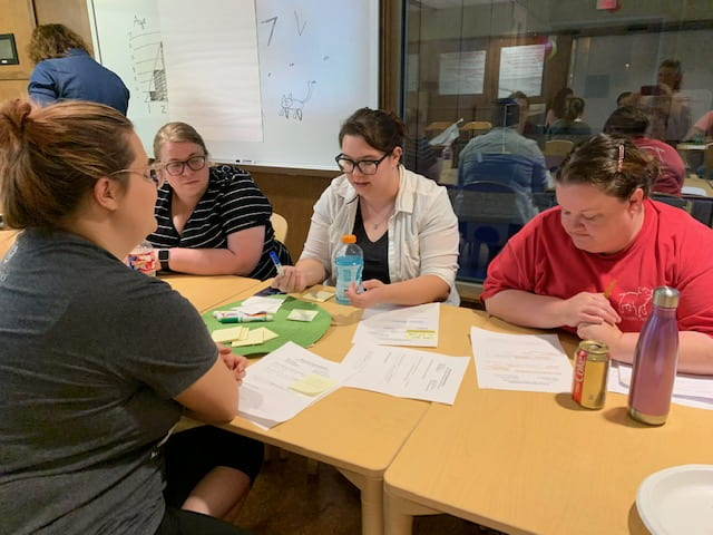 Four women are sitting at a table looking at their papers during a workshop at the September Professional Educator Development Day at the Jean Tyson Child Development Study Center at the University of Arkansas. Another woman is standing in the background.