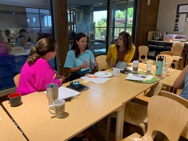 Three women sit at a table, the one sitting in the middle is talking while the others look at her during the September Professional Educator Development Day at the Jean Tyson Child Development Study Center at the University of Arkansas.