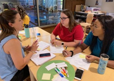Three women sit at a table writing on paper and talking during the September Professional Educator Development Day at the Jean Tyson Child Development Study Center at the University of Arkansas.