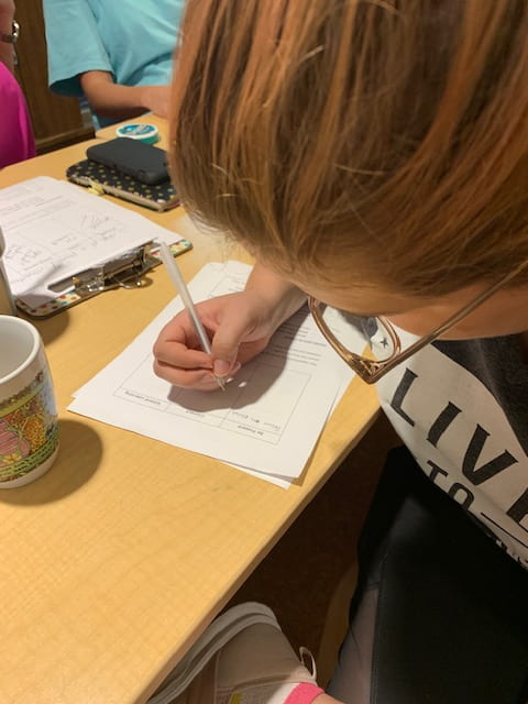 A woman leans over a table to write on a piece of paper during the September Professional Educator Development Day at the Jean Tyson Child Development Study Center at the University of Arkansas.