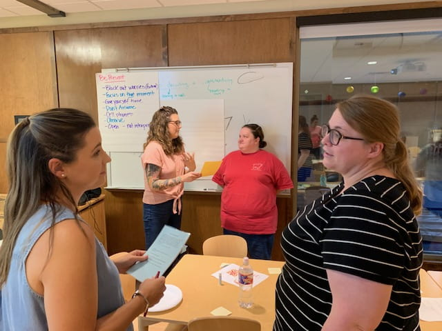 Two women in the foreground and two women in the background having discussions during the September Professional Educator Development Day at the Jean Tyson Child Development Study Center at the University of Arkansas.