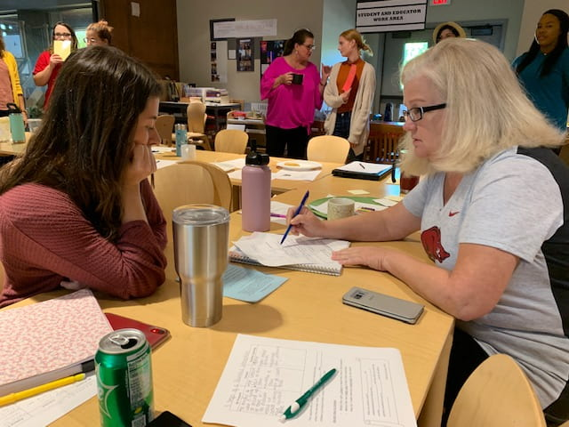 Two women sitting at a table during a workshop for the September Professional Educator Development Day at the Jean Tyson Child Development Study Center at the University of Arkansas. Other women stand in the background.