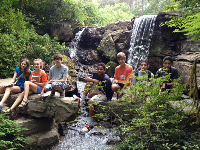 Participants of Design Camp sit in front of a waterfall at Garvan Woodland Gardens in Hot Springs.