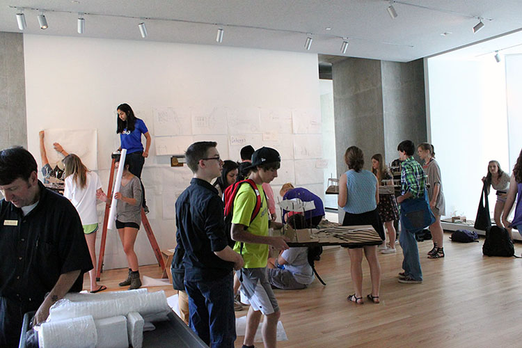 Students hang up their drawings and prepare their models for the final exhibition at the closing reception in Smith Exhibition Gallery of Vol Walker Hall. (Photo by Julia Trupp)