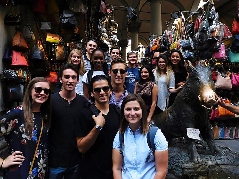 "Students pose for a group shot with ""Il Porcellino"", the bronze statue of a boar. Walsh says that everyone loved Florence and thought it was ""modern"" in comparison to Rome."
