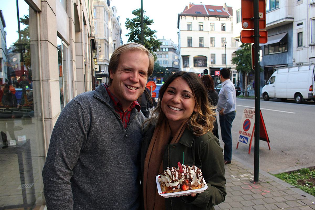 "Students are encouraged to travel on their ""open"" three-day weekends, and here Joshua Powell and Kelly Walsh are shown in Brussels, Belgium. Walsh says they chose Brussels for the Belgium waffles (one of them shown), and it ended up being her favorite city to that point."