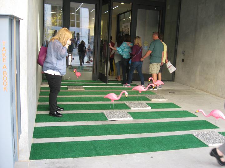 Professor Kim Furlong walks through the pink flamingo portion of Kelsey Winters and Natalie Vitek's project. (Photo by Mattie Bailey)