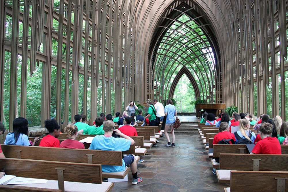 Students sit inside Mildred B. Cooper Memorial Chapel, a design by Fay Jones, in Bella Vista.