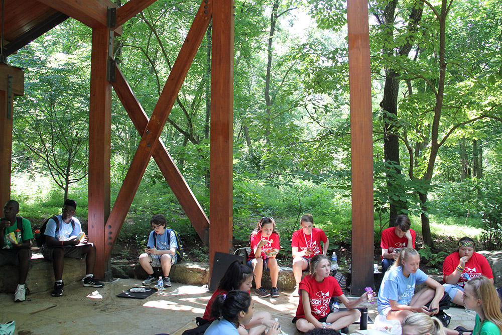 Students eat lunch under the Tulip Tree Shelter, located along a trail about 300 yards south of Crystal Bridges museum. Its original function was as a mockup for the roof of the museum's Great Hall.