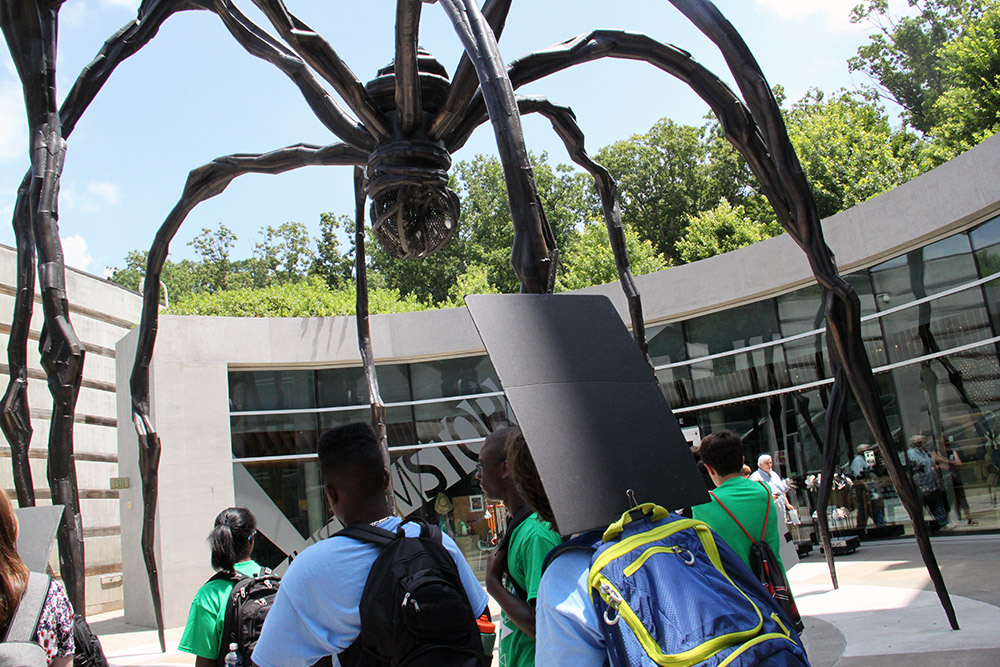 "Students gather in the courtyard entryway at Crystal Bridges Museum of American Art in Bentonville. ""Maman,"" created by the sculptor Louise Bourgeois in 1999, is made from bronze, stainless steel and marble."