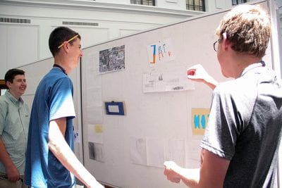Students pin up their work for the final review and reception held June 15.