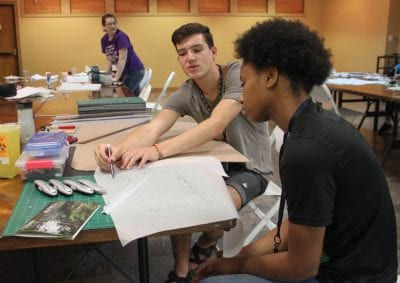 Fay Jones School student Beau Burris shows a Design Camp student how to finish the next step in her project.