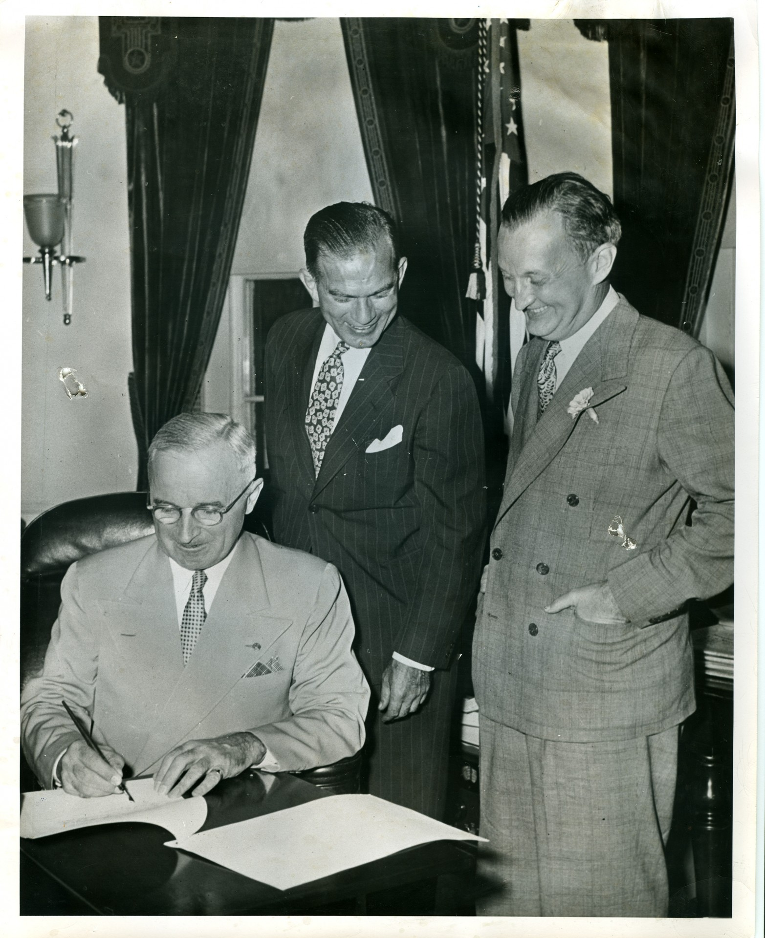 Senator Fulbright and Assistant Secretary of State William Benton look on as President Harry S. Truman signs the Fulbright Act into law, August 1, 1946. From the J. William Fulbright Papers, S86 Box 9 Folder 1, Special Collections, University of Arkansas Libraries.