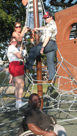 4 people climb on playground equipment while man in wheelchair sits in front of it